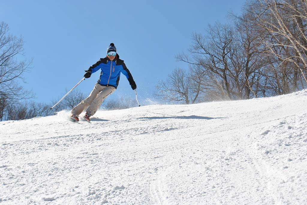 Man in blue jacket skiing at Catamount